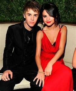 this is selena with hairstyle and dress siting by justin bieber