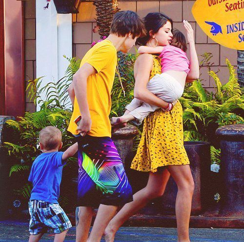 mine WITH A CELEBRITY-JUSTIN BIEBER.... WEARING A DRESS-YELLOW.... AND HOLDING SOMETHING-JUSTIN'S SISTER....