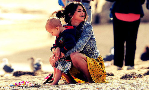 This is mine. Selena looks so happy when she plays with Justin's little brother. It's so cute! :)