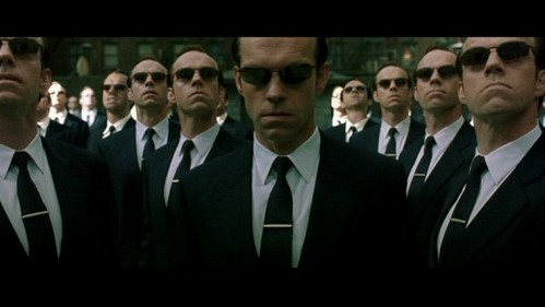 Post a picture of a fictional character in a black suit and sunglasses.