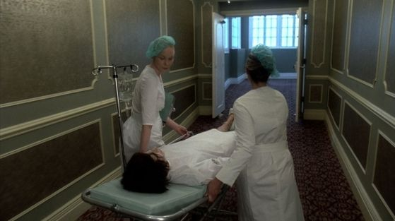 GaGa is lying on a gurney being wheeled through a hallway by two nurses wearing mint Parisian berets.