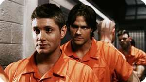 Dean and Sam in orange jumpsuits
