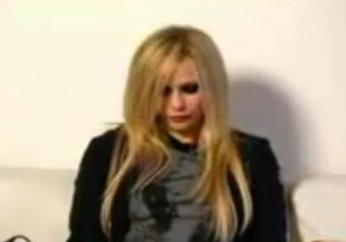 Avril covering her breasts with her hands