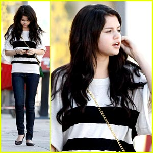 Selena down the street on her iPhone