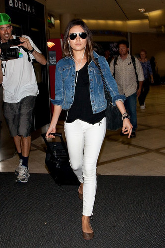 Mila Kunis arrives at LAX (Los Angeles International Airport) with her headphones plugged in.