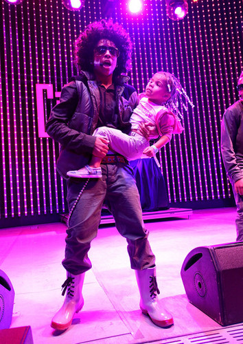 Prince holdin a lil girl while performin