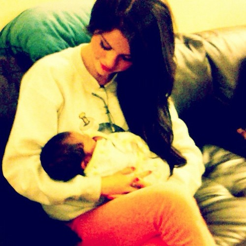 She gomez holding her friend baby :)