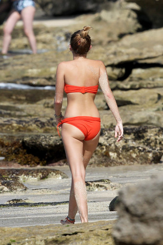 Miley Cyrus wallpaper possibly containing a bikini called Miley - 29. December - On a beach with Liam Hemsworth in Hawaii