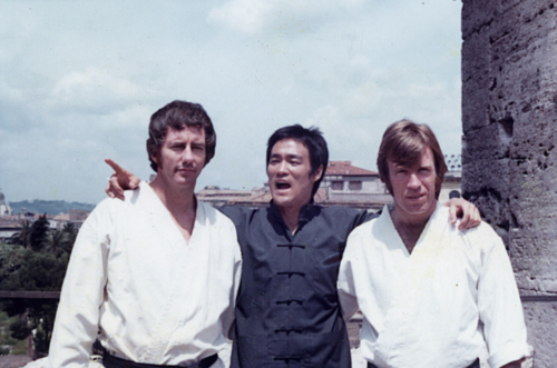 Bruce Lee wallpaper probably with a street, a portcullis, and a well dressed person titled Way of the Dragon,behind the scenes