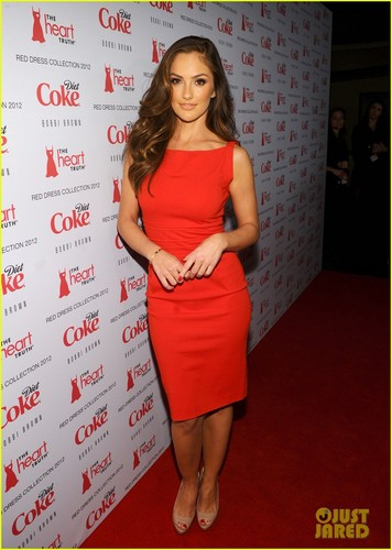 Minka Kelly achtergrond possibly containing bare legs, a cocktail dress, and a sign titled Minka Kelly: hart-, hart Truth's Red Dress Fashion Show!