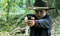 carl with a gun wearing his hat
