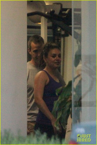Mila Kunis wallpaper with a revolving door titled Mila Kunis Calls Ashton Kutcher Dating Rumors 'Absurd'