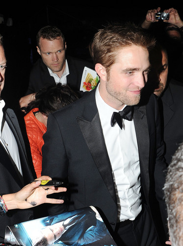 Robert Pattinson & Kristen Stewart wallpaper probably containing a business suit titled holding hands at Cosmopolis afterparty