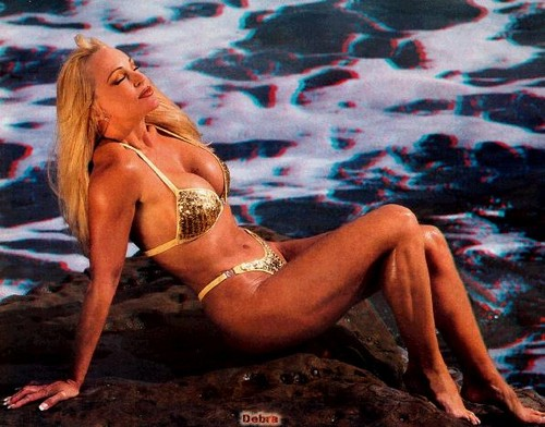 Debra in a tiny gold bikini