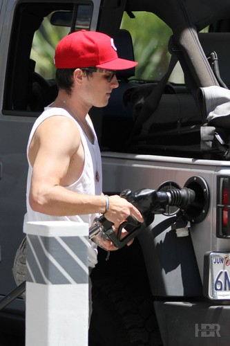 Josh puts gas in his car with his dog, Driver.