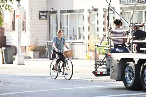 "Keira riding a bicycle during a scene for ""Can a Song Save Your Life?"" in Brooklyn (July 25)"
