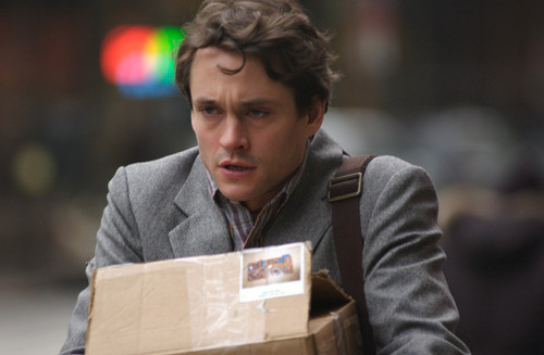 Hugh Dancy Hintergrund with a packing box and a business suit titled Adam