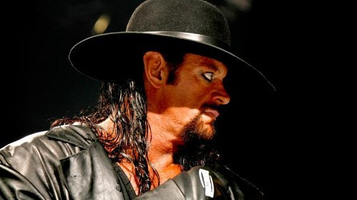 Undertaker achtergrond with a fedora, a boater, and a dress hat called Taker