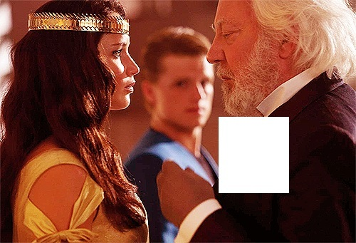 What color rose is President Snow wearing in this image?