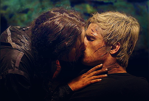 On what page in The Hunger Games did Katniss kiss Peeta in the cave?
