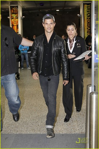 Taylor Lautner flashes his pearly whites as he walks through the airport on Saturday (August 20)