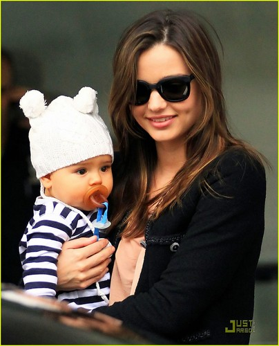 Miranda Kerr carries her adorable son Flynn while catching a departing flight at the airport