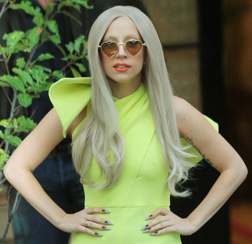 Lady Gaga greets her fans before she leaves the Lanesborough Hotel in London.